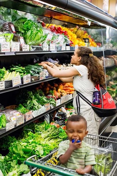 Woman looks through vegetables at co-op
